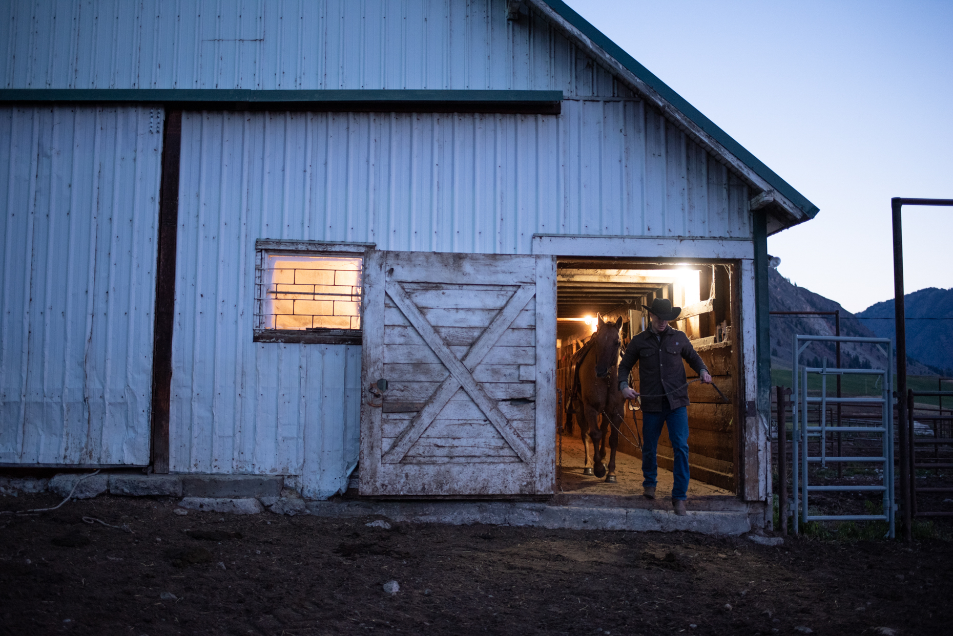 Cowboy and horse leaving barn before sunrise on a northern Washington cattle ranch. Isaac Miller Photography  | Agriculture & Industry Photographer  |  Commercial & Editorial photography  |   Missoula + San Antonio